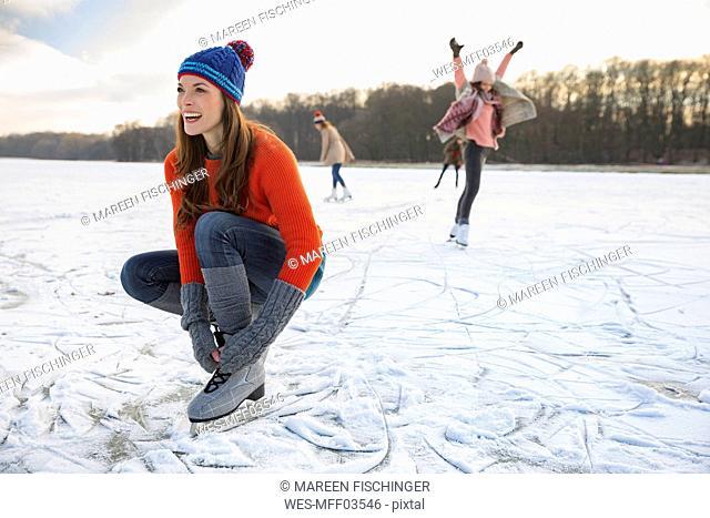 Woman tying her ice skates on frozen lake