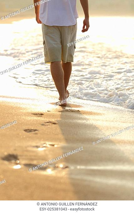 Backlight of a man legs walking on the beach leaving footprints