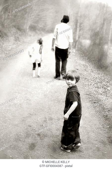 child looking back as family walks down path