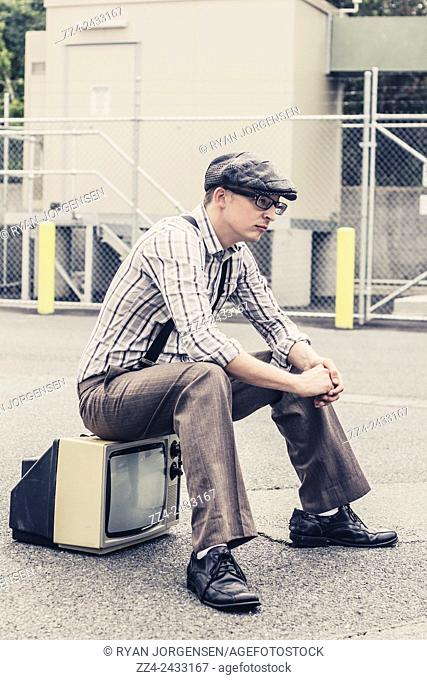Antique stylised photography of a serious nerd sitting on retro tv. Technology grief