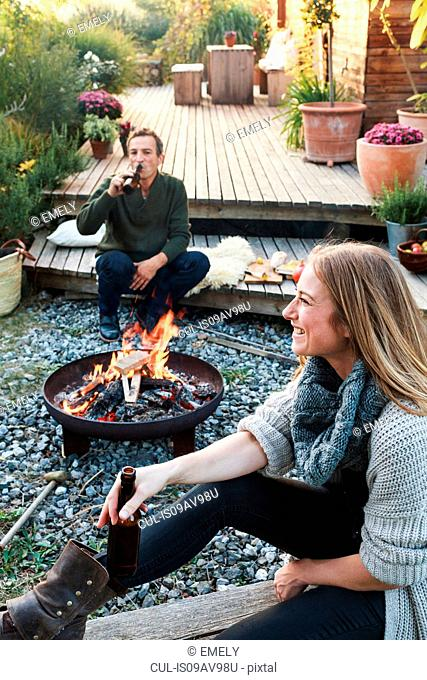 Man and woman sitting by fire pit with beer, relaxing