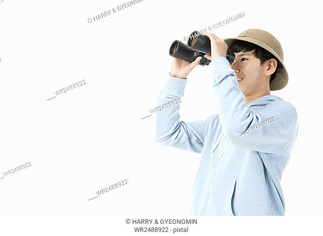 Side view portrait of smiling school boy looking through binoculars
