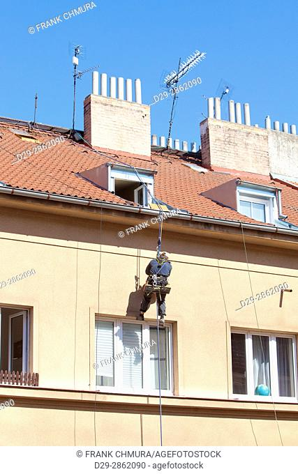 Maintenance Worker with Safety Strap on a House Roof