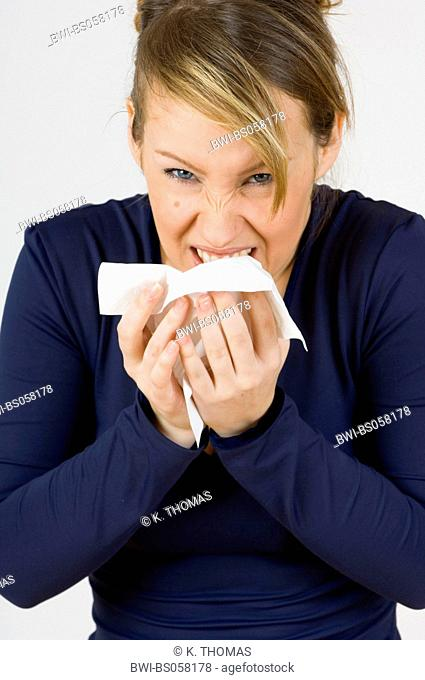 young woman cleaning her nose with a handkerchief