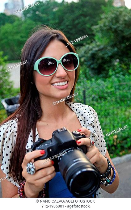 Attractive young mixed race woman using a DSLR camera in Central Park, New York City