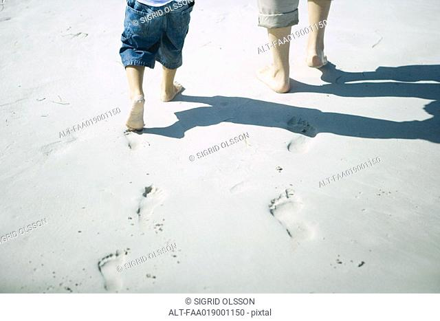 Child and adult walking on sand, low section