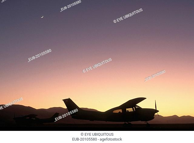 A cessna aircraft in the desert silhouetted at sunset