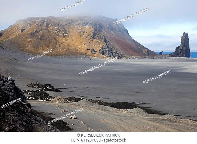 Rhyolite mountain and volcanic plug / volcanic neck / lava neck on beach of Jan Mayen, island in the Arctic Ocean in spring