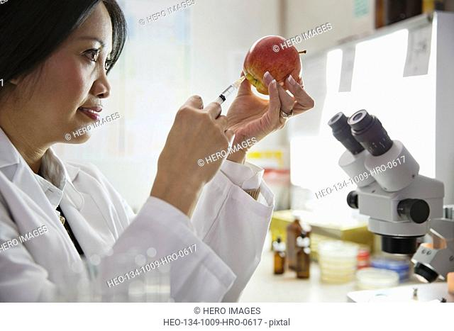 Female scientist injecting liquid into an apple in laboratory