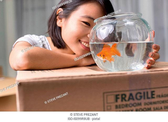 Young woman looking at goldfish on moving box