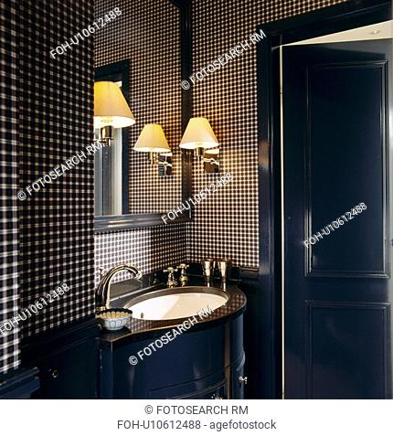 Wall-light above basin in cloakroom with black+white checked wallpaper