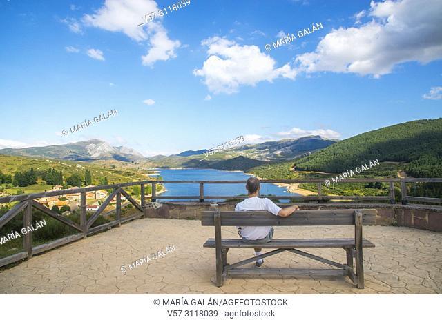 Man sitting on bench at the viewpoint over Camporredondo reservoir. Alba de los Cardaños, Palencia province, Castilla Leon, Spain