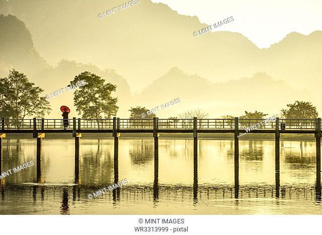 Mountains and bridge reflected in still lake, Hpa an, Kayin, Myanmar