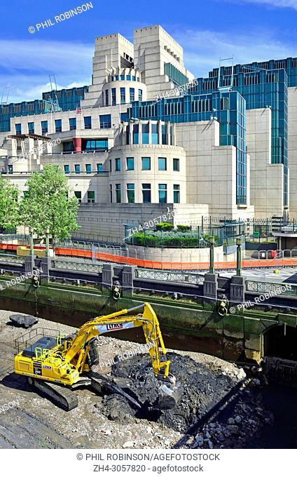 London,England, UK. SIS Building / MI6 headquarters at Vauxhall Cross. Excavator digging on the beach below at low tide