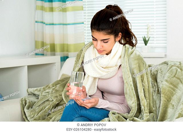 Sick young woman covered with blanket holding glass of water on sofa at home