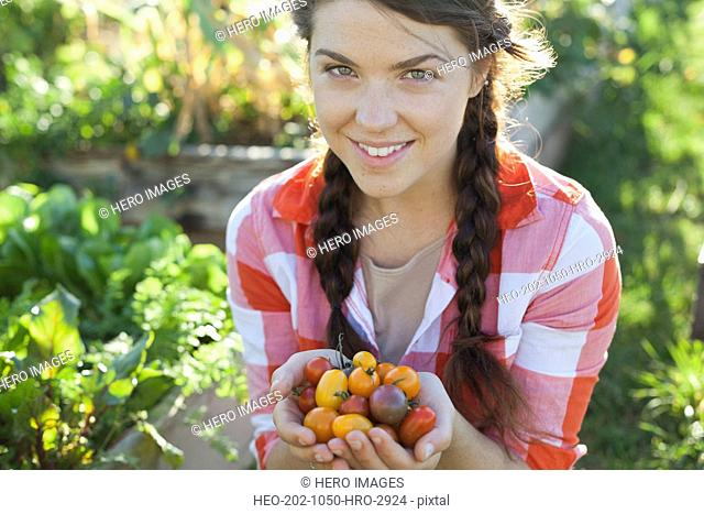 Portrait of woman with handful of cherry tomatoes