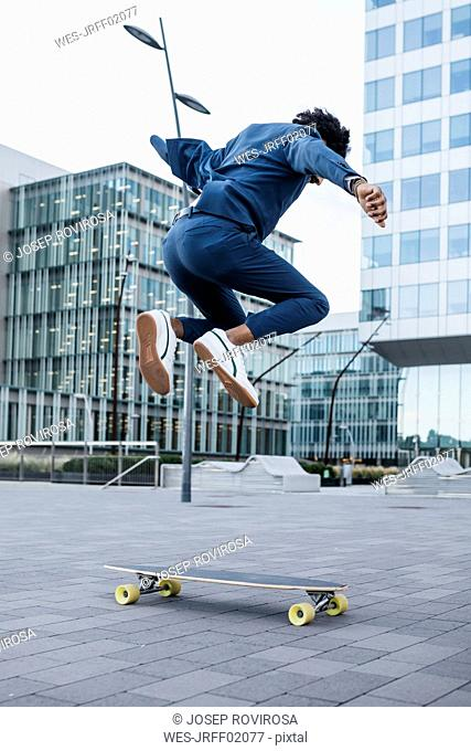 Spain, Barcelona, young businessman doing skateboard tricks in the city