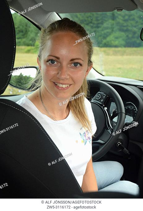 Young smiling woman in a car, looking direkt in the camera, on a countryroad in Scania, Sweden, Europe