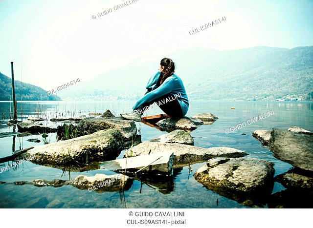 Young woman sitting on rock looking out over Lake Mergozzo, Verbania, Piemonte, Italy