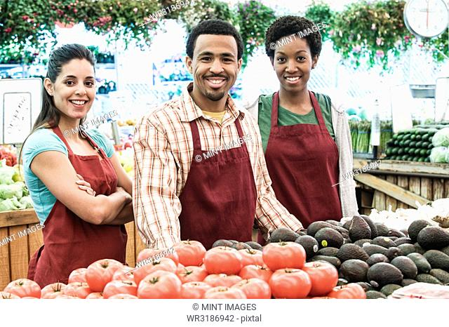 Man and two women wearing aprons standing at stall with fresh tomatoes at a fruit and vegetable market