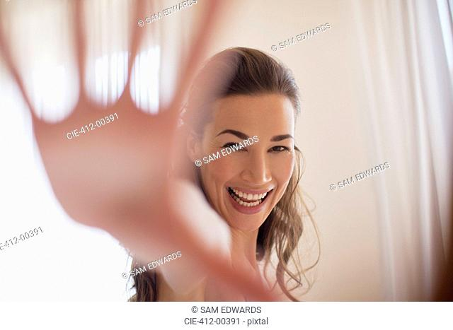 Portrait of smiling woman with hand outstretched