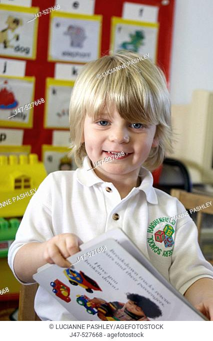 blonde haired, 4 year old boy smiling into camera at nursery