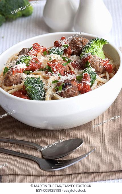 Beef meatballs with spaghetti and broccoli topped with grated Parmesan