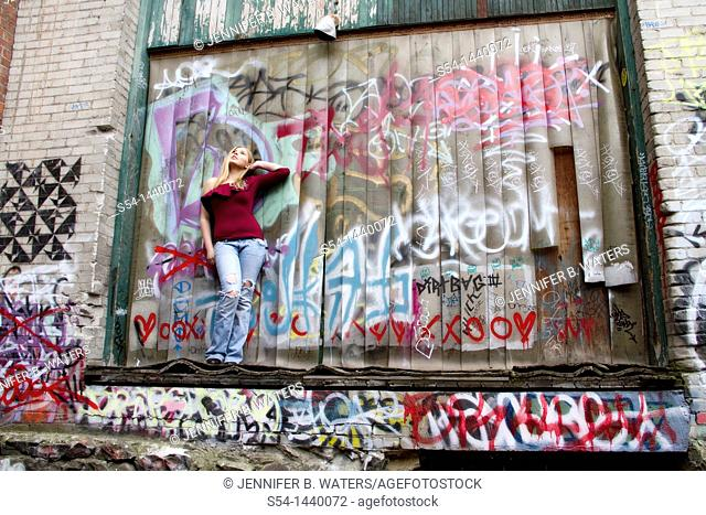A young woman standing in an alley in Spokane, Washington, USA