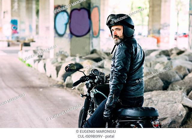 Portrait of mature male motorcyclist looking over his shoulder from motorcycle under flyover