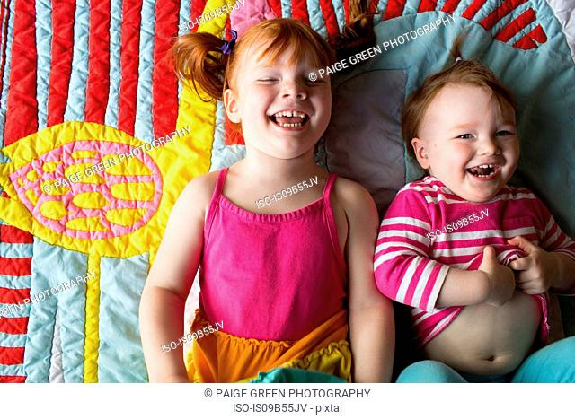 Portrait of two young sisters lying on blanket, laughing