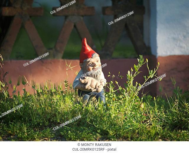 Garden gnome holding piglet