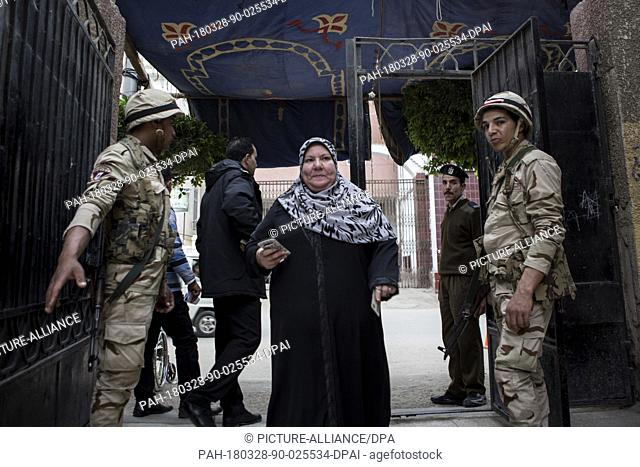 dpatop - An Egyptian woman walks past army soldiers as she enters a polling station to vote on the 3rd day of the 2018 Egyptian presidential elections