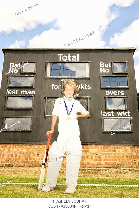Boy Cricketer with medals and scoreboard