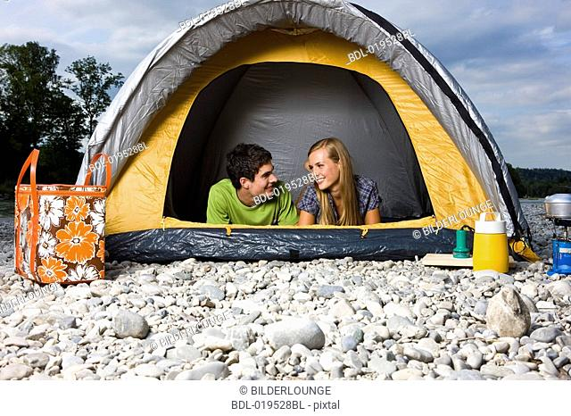 young couple lying in tent looking at each other & Young couple in tent camping kissing Stock Photo Picture And ...