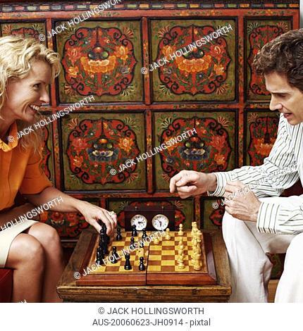 Side profile of a businessman and a businesswoman playing chess