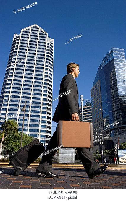 Businessman walking with luggage in urban setting