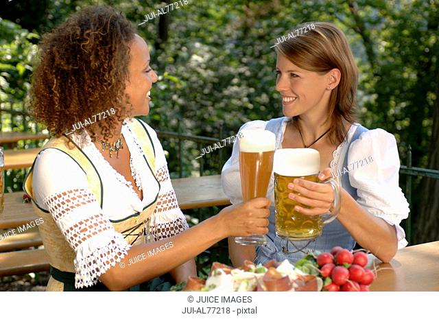 View of two young women toasting each other, beergarden, Munich, Bavaria, Germany