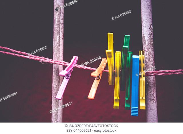 Vintage view of colorful Clothes pegs pinned to a bench with red wall in a background hanging on a clothes rack