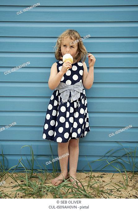 Young girl enjoying ice cream next to beach hut