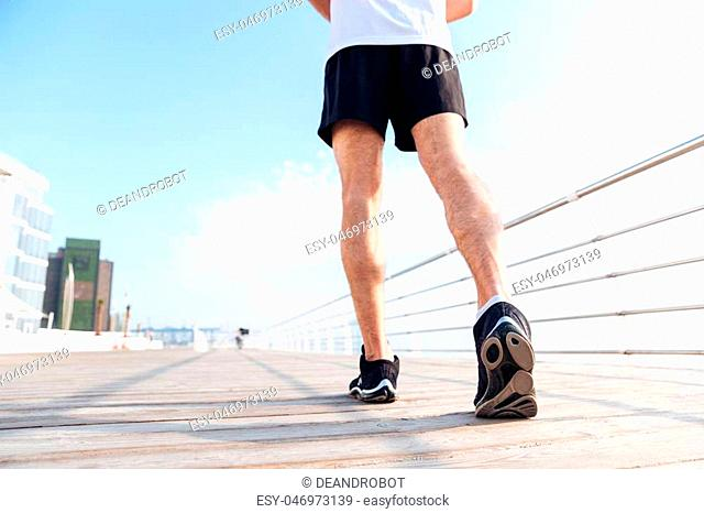 Back view of legs of young man in black shorts and sneakers running on pier