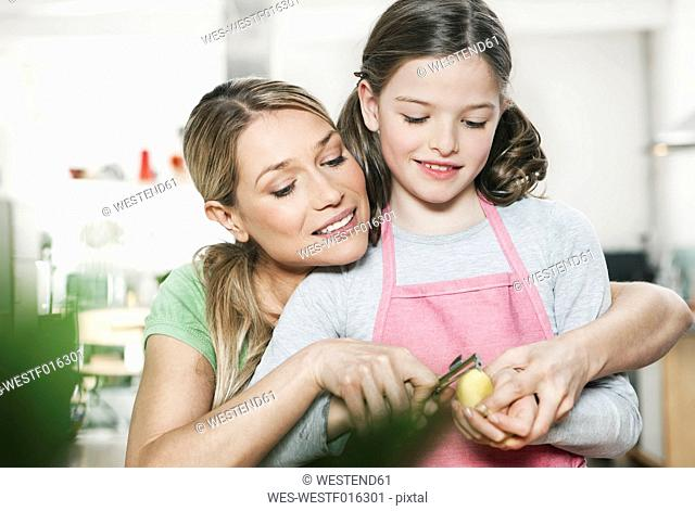 Germany, Cologne, Mother and daughter peeling potato