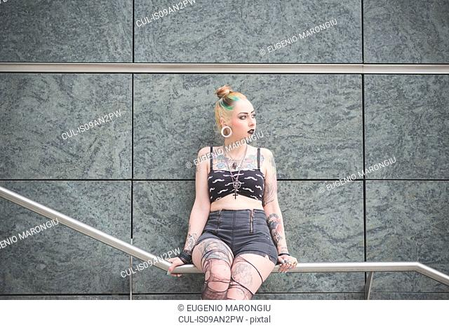 Portrait of young female tattooed punk sitting on subway railing