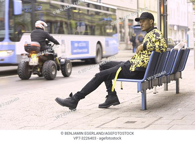 man sitting on bench in city, streetstyle, in Munich, Germany