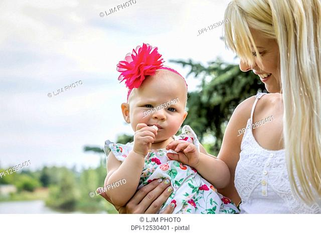 A beautiful young mother with long blonde hair enjoying quality time with her cute baby daughter in a city park on a summer day; Edmonton, Alberta, Canada