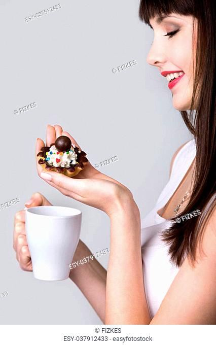 Young smiling woman holding in her hands cup of coffee and tart cake with cream and chocolate, beautiful cheerful female teen model enjoying lunch, studio