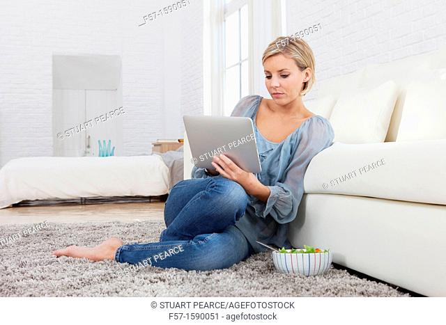 Young woman having lunch while socializing on her tablet computer