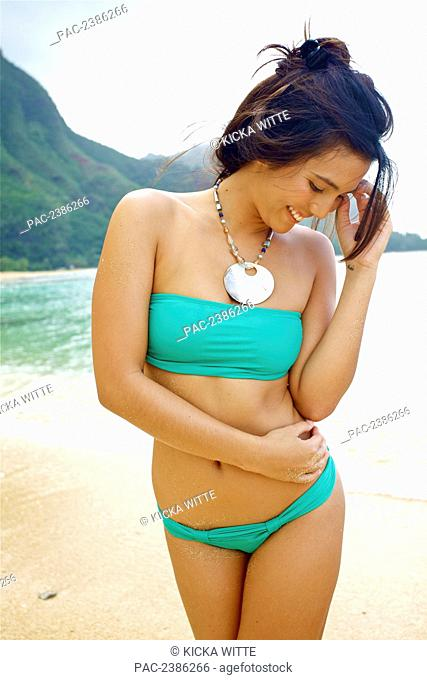 Portrait of a young woman in a bikini with long brunette hair on the beach; Kauai, Hawaii, United States of America