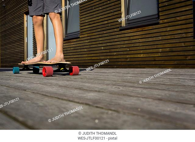 Legs of boy standing on his skateboard