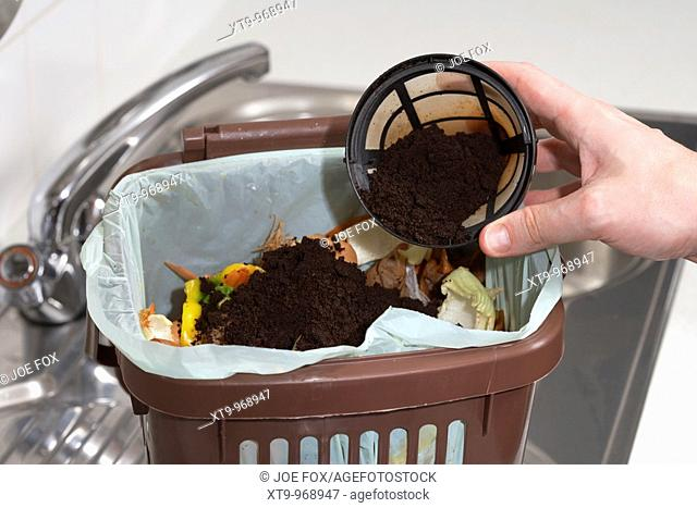 putting used coffee grounds into a kitchen home compost food recycling bin in the uk