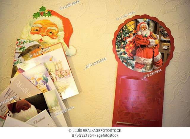 Cristmas cards with a picture of Santa Claus hunging on a wall of a house, England, UK, Europe